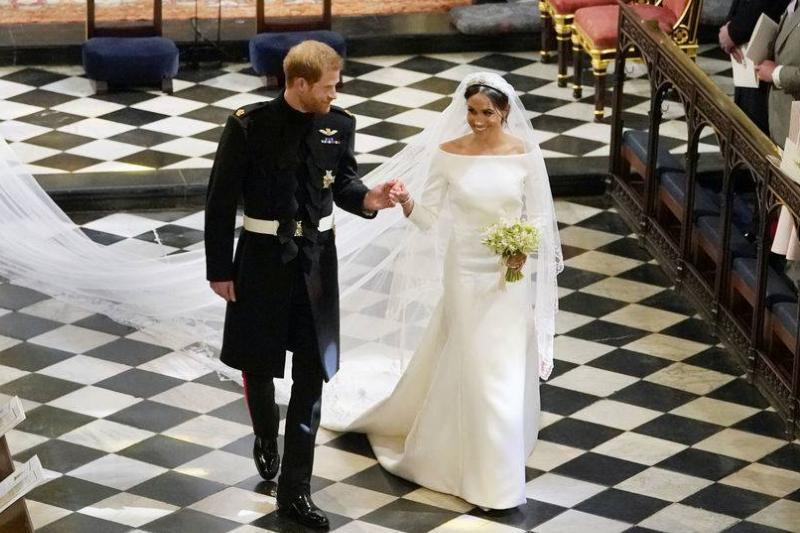 Prince Harry and Duchess Meghan walk down the aisle after getting married.