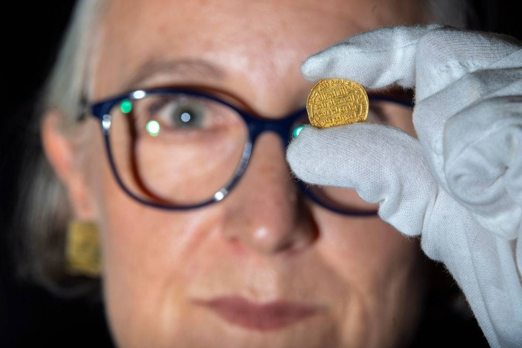 A member of staff at Morton & Eden holds an extremely rare early Islamic gold coin