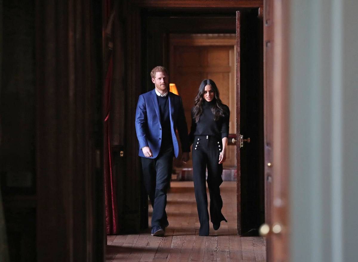 Prince Harry and Meghan Markle walk through a corridor of the Palace.