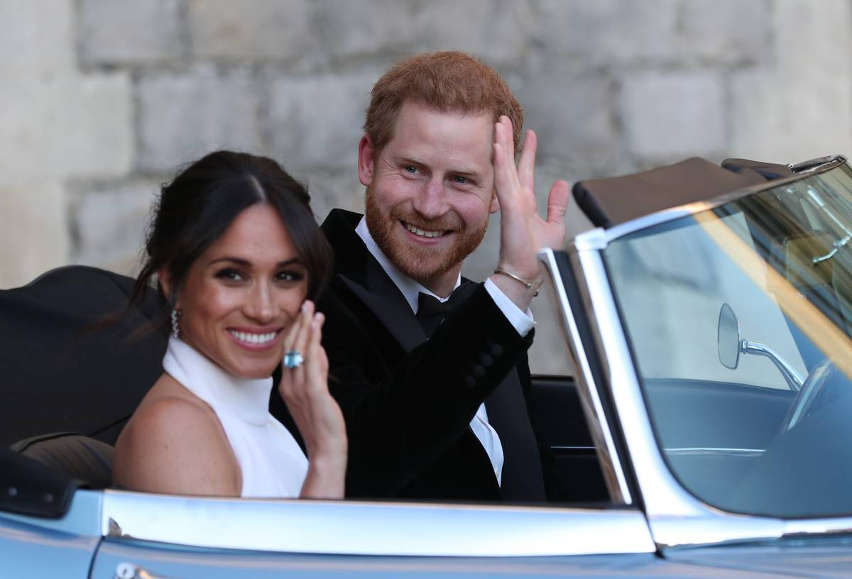 Duchess Meghan and Prince Harry wave as they leave their wedding in a car.