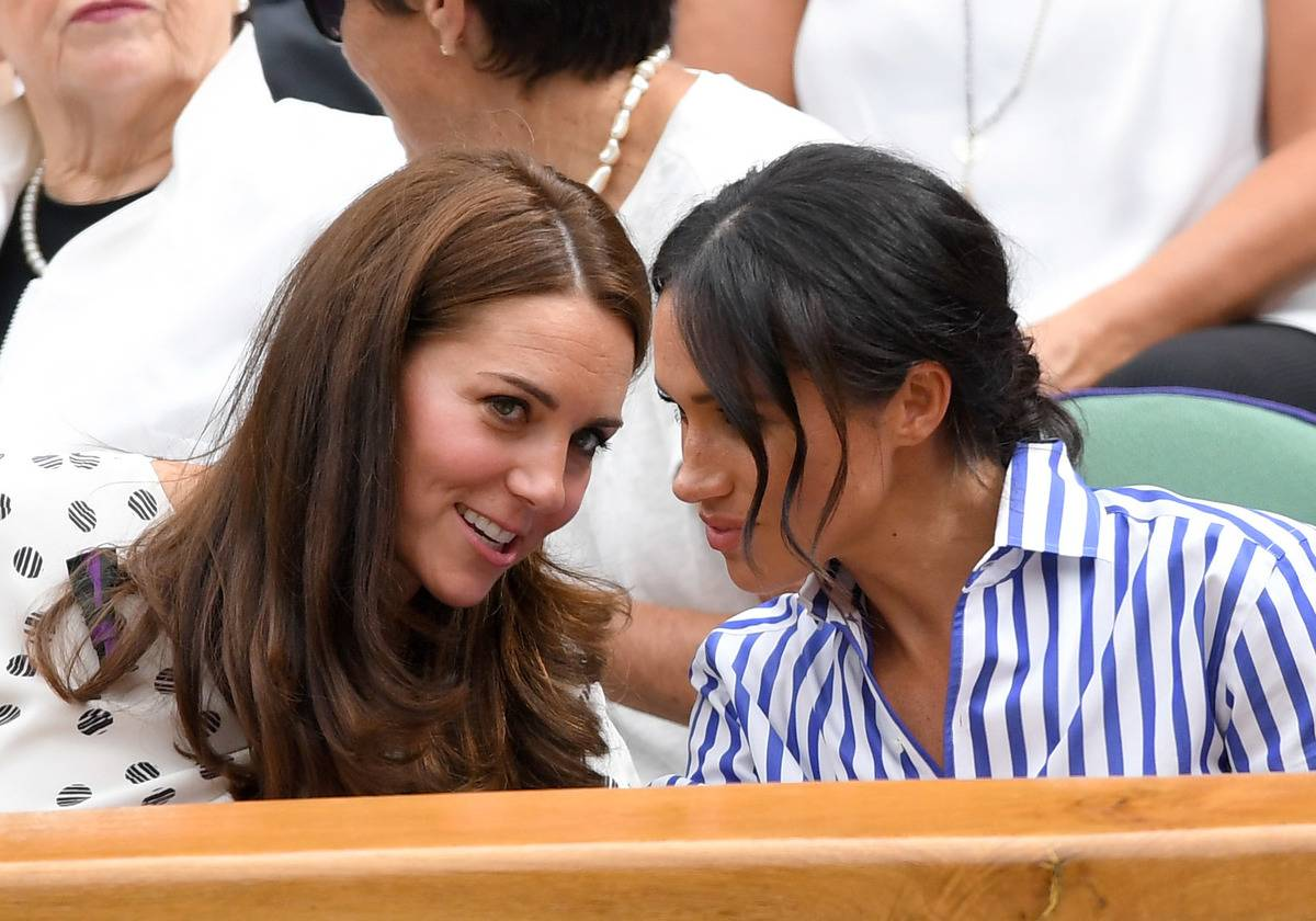Kate Middleton whispers to Meghan Markle at the Wimbledon Tennis Championships.