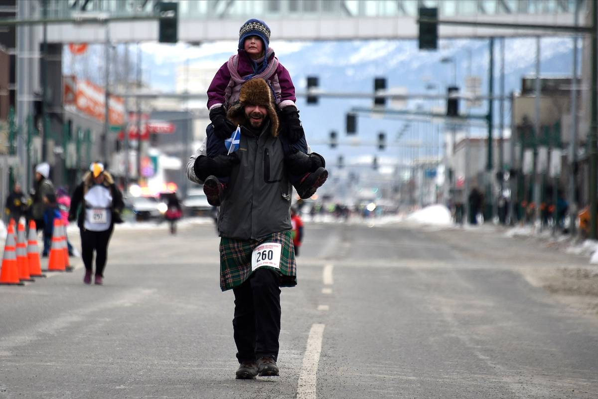 A man runs with his daughter on his shoulders in Alaska.
