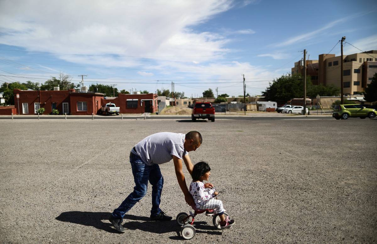 A father pushes his daughter on a bike in a New Mexico parking lot.