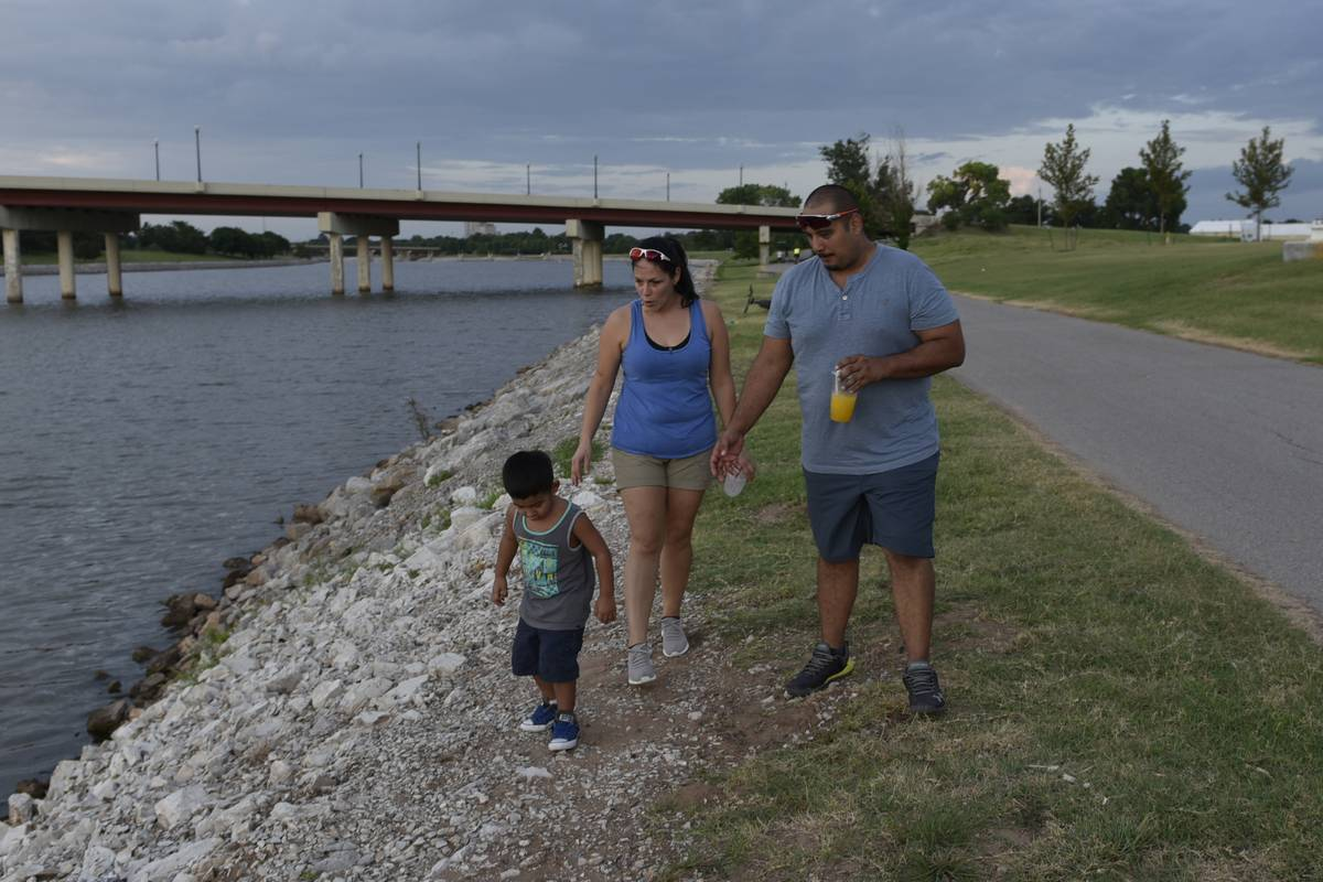 A family with a young child walks next to the river in Oklahoma City.