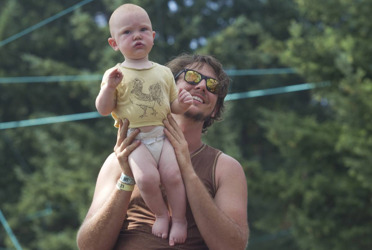 A man at the Pickethon music festival in Oregon holds up his baby.