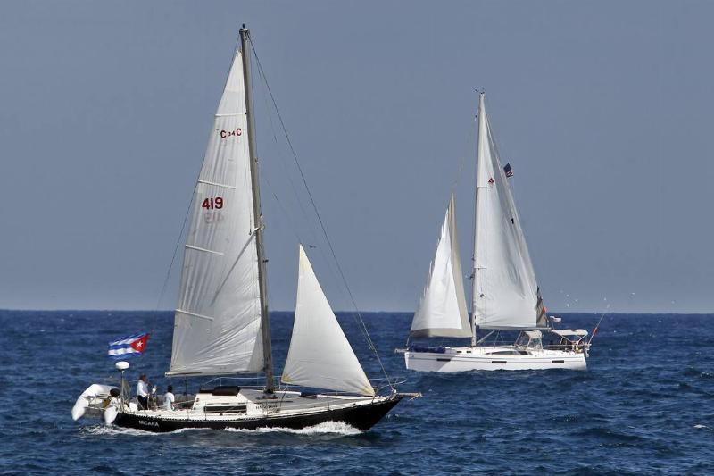 Cuban sailboats glide along the ocean.