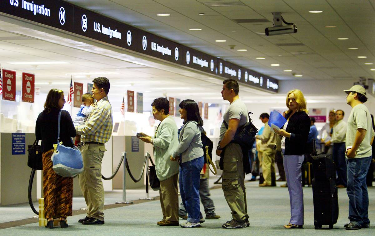 In Miami, people stand in line to be checked by Immigration inspectors.