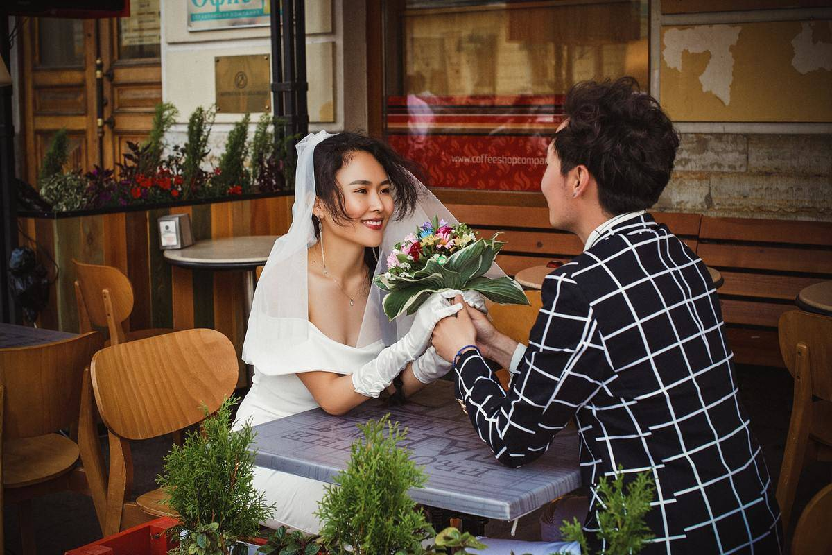 Newlywed couple sitting at restaurant patio table. Woman wearing white dress, gloves, and veil, holding bouquet. Man wearing checked black suit jacket. Both smiling