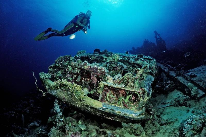 Divers swim by a sunken Toyota, part of the Blue Belt Shipwreck.