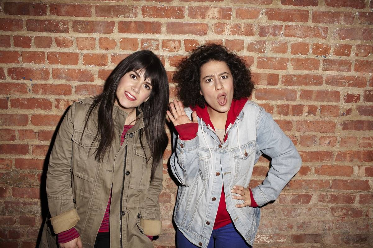 Abbi Jacobson and Ilana Glazer standing in front of a brick wall on broad city