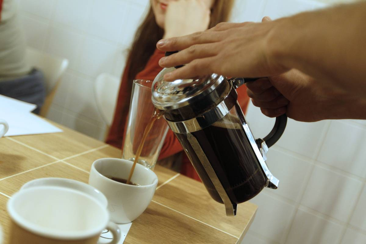A waiter pours hot coffee into a mug at a restaurant.