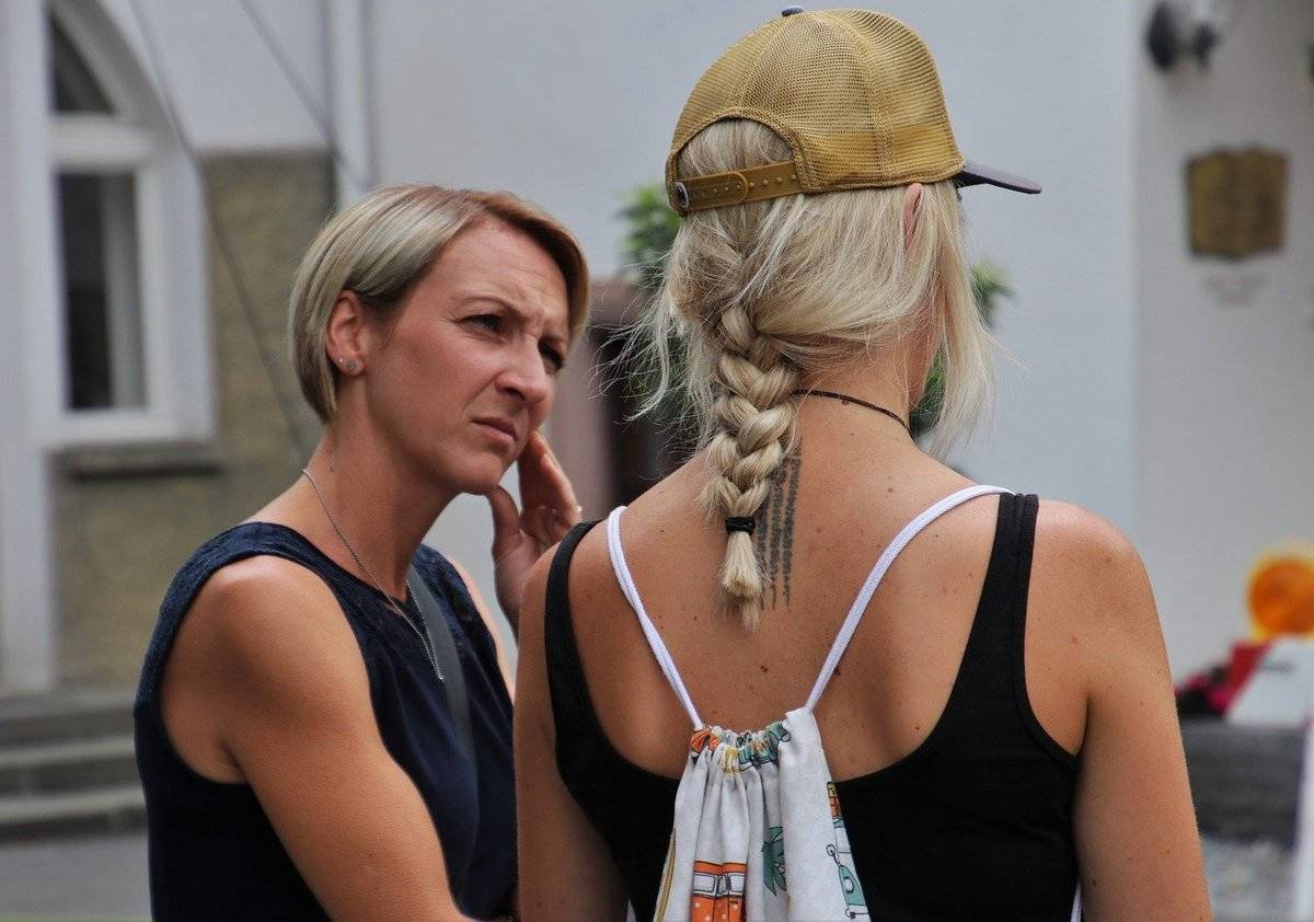 A woman appears concerned and confused while speaking to another woman.