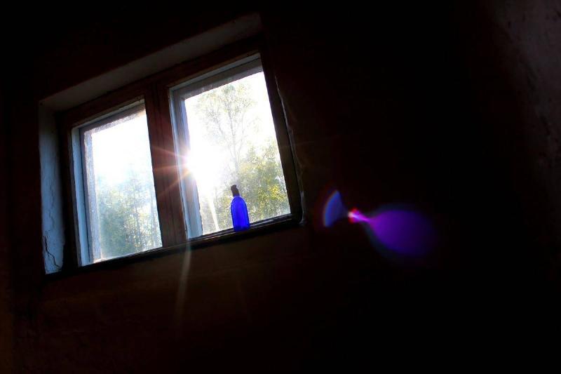 Sun shines through an open window into a dark room.