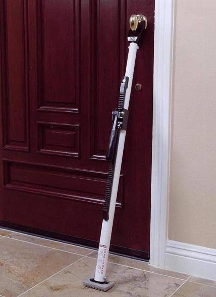 A door security bar is propped between the door knob and floor.
