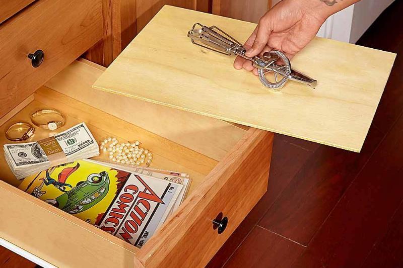 A person picks up the false bottom of a dresser drawer.