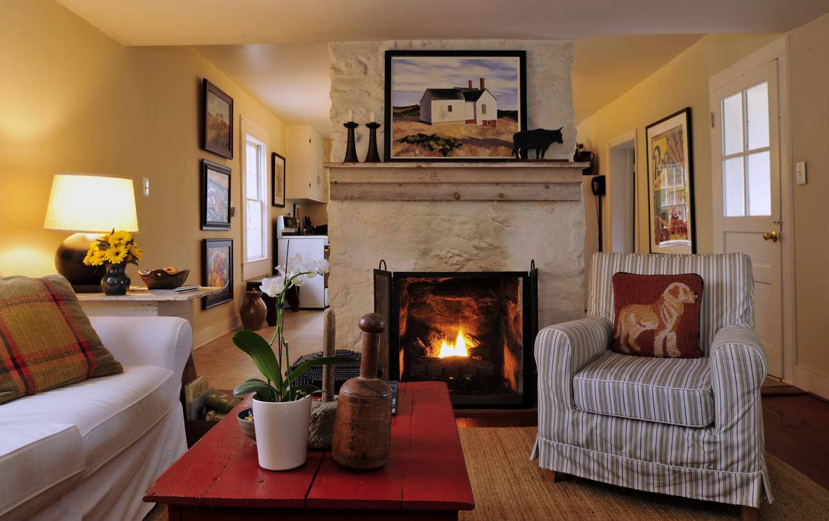 A farmhouse has rural decor, like a fireplace, painting of a farmhouse, bull statue, and red coffee table.