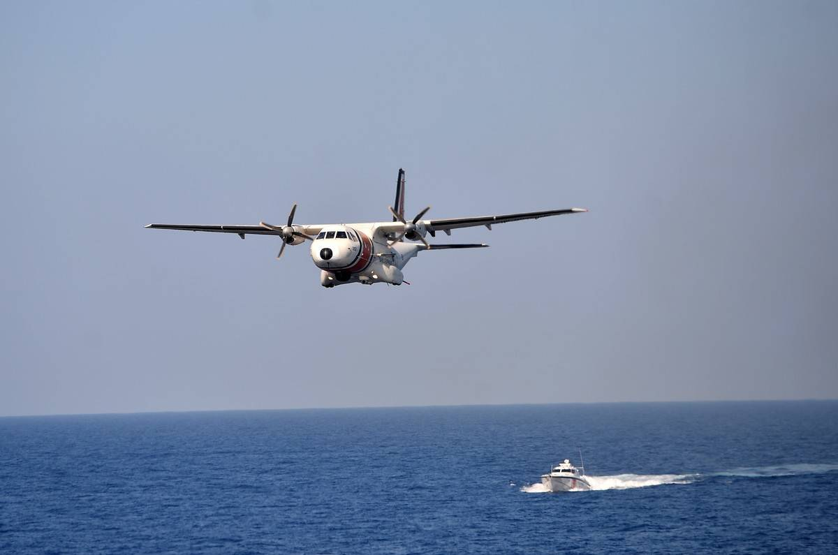 The Coast Guard flies on a plane over the ocean.