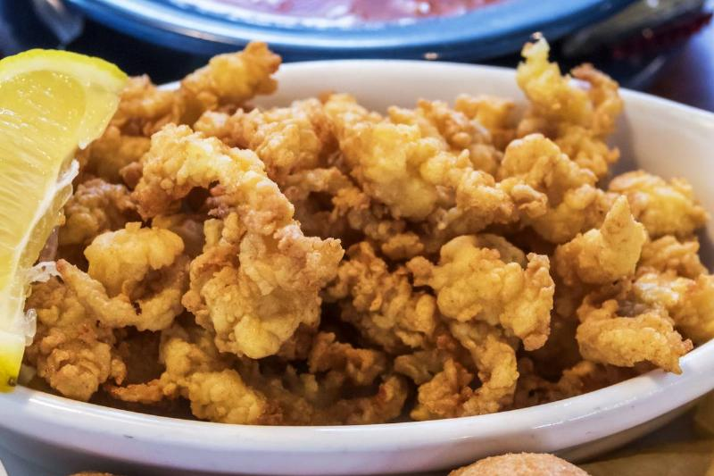Fried clams and hush puppies are portrayed next to sauce in a North Carolina restaurant.