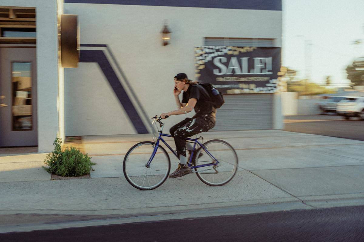 A man hurries while riding his bike and talking on the phone.