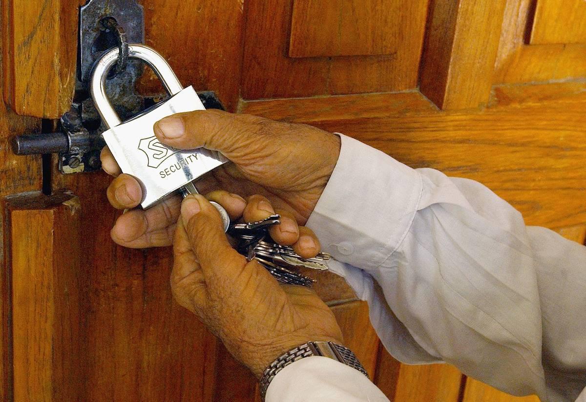A man locks a door with a padlock.