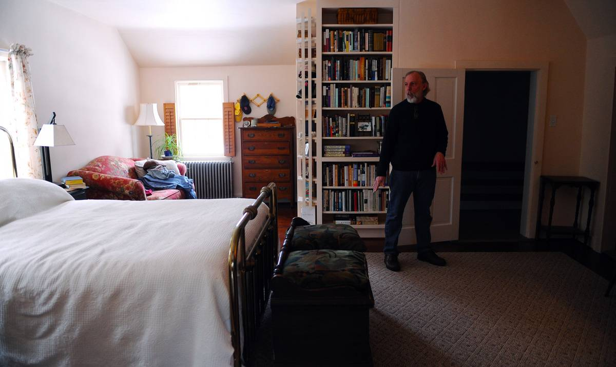 A man stands near the door in his master bedroom.