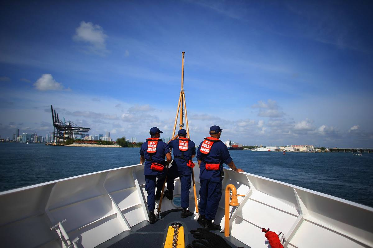 Three members of the Miami Coast Guard stand at the front of a boat.