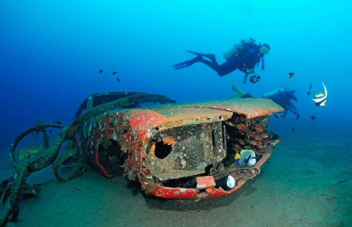 A diver swims by a 1970 Mustang underwater.