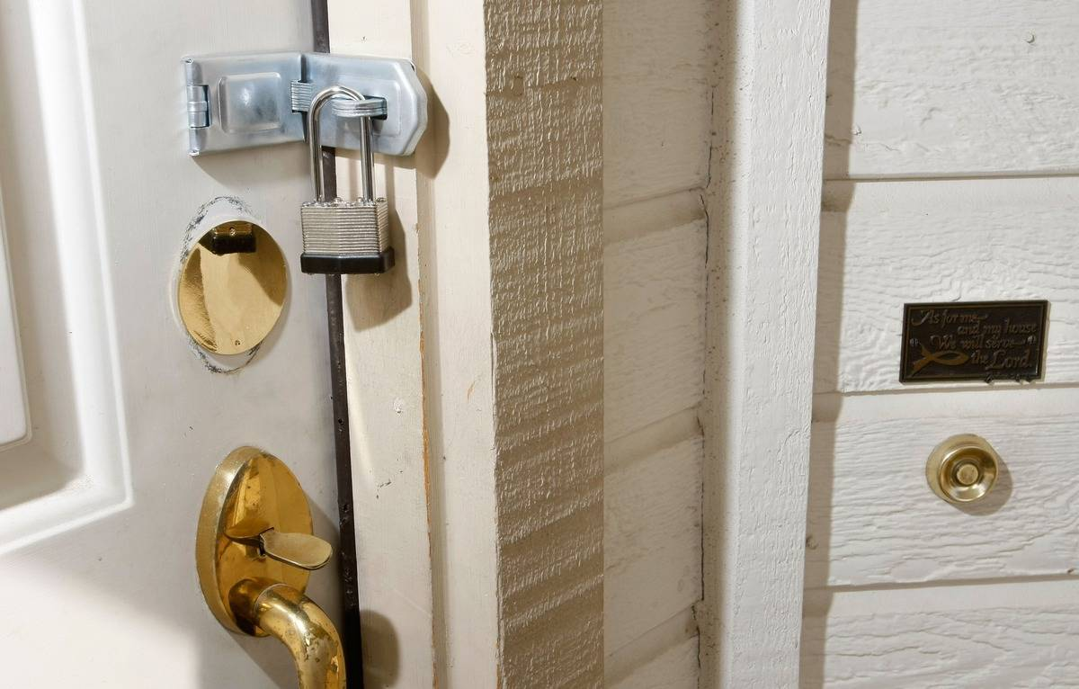 The front door of a home is secured with a stainless steel padlock.