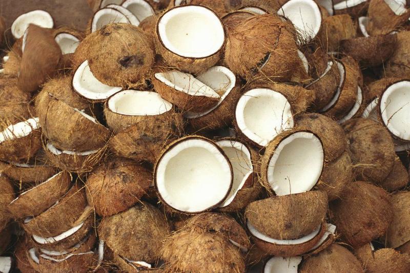 Halves of split coconuts lie in a pile.