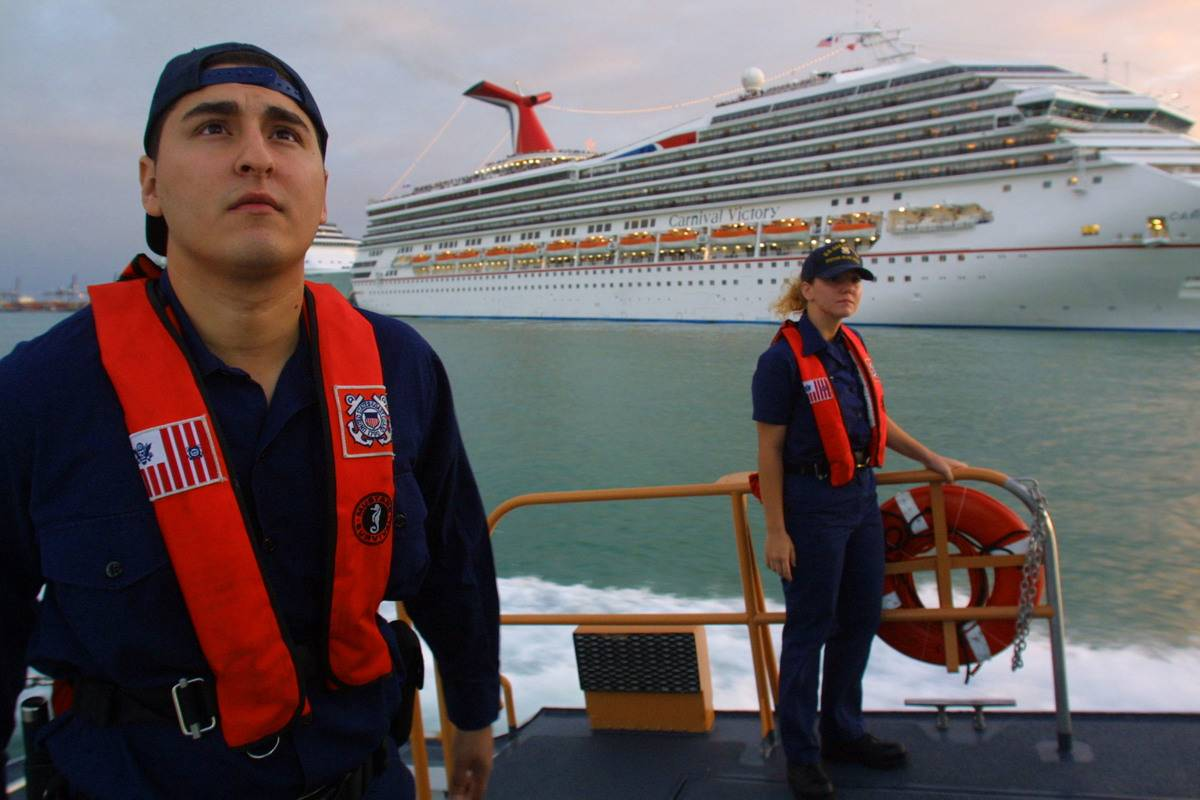 Coast guard members sail by a ship for security.