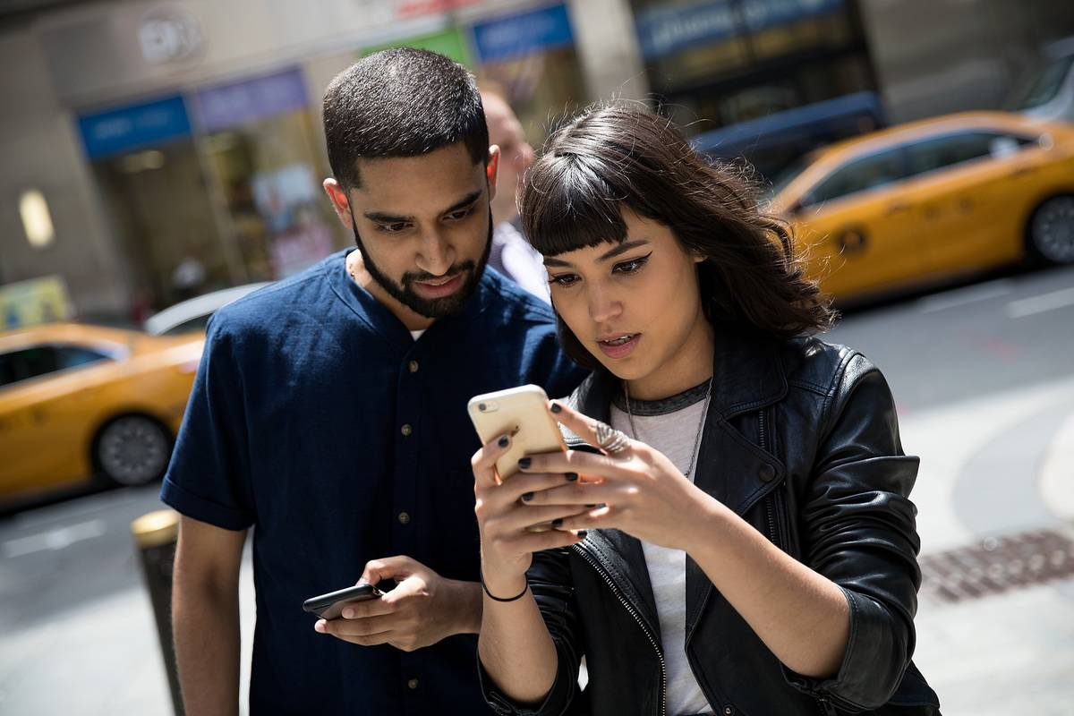 A couple looks at a woman's smartphone, astonished.