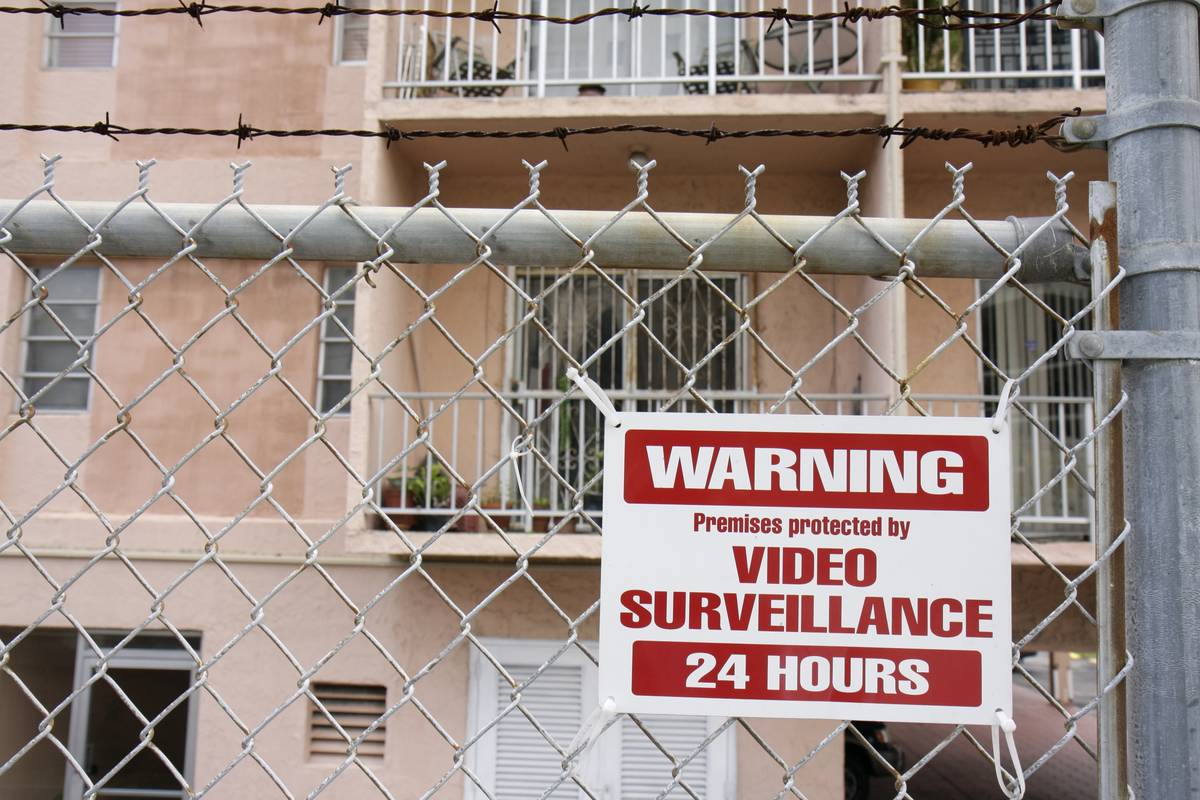 A warning sign on a fence says the home has security.