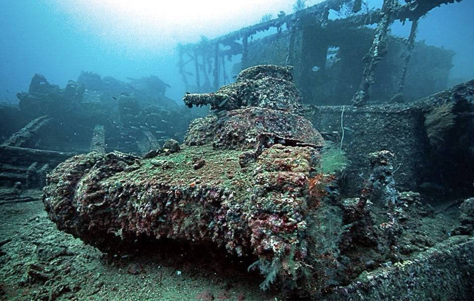 An underwater tank from World War II is covered with barnacles and moss.