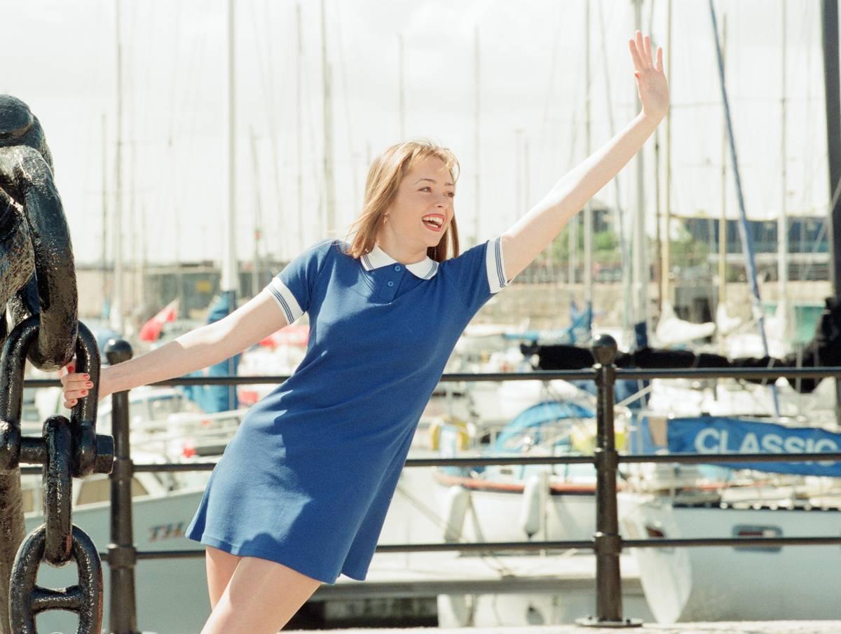A woman waves to someone at a marina.