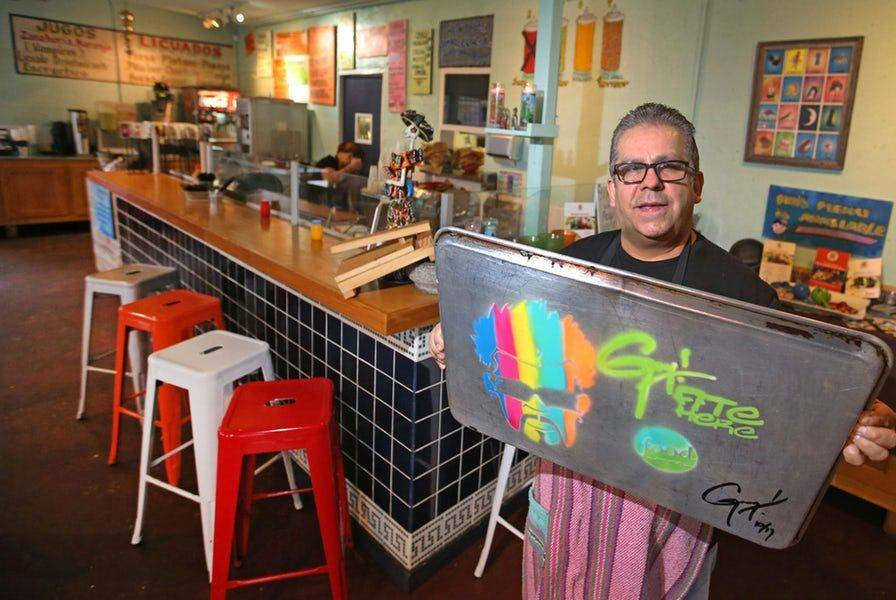 A restaurant owner holds up a baking tray with Guy Fieri's Triple D spray paint artwork on the back.