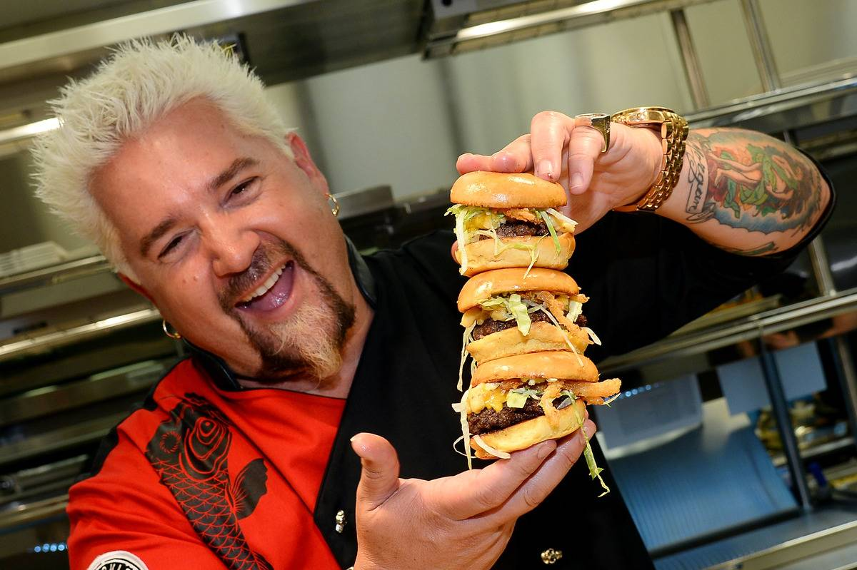 Guy Fieri holds a stack of hamburgers during Guy Fieri's Vegas Kitchen & Bar in 2014.