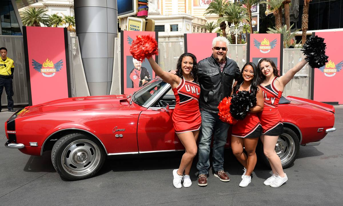 Guy Fieri poses with cheerleaders next to his red Camaro.