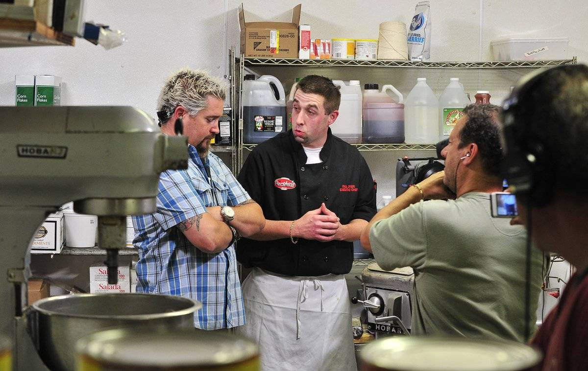 While filming Food Network/Diners, Drive-Ins And Dives, Guy Fieri speaks to a chef at Port Hole Restaurant.