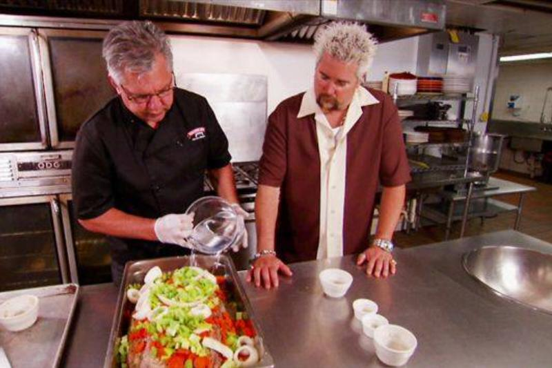Guy Fieri watches a chef mix season vegetables on Diners, Drive-ins and Dives.