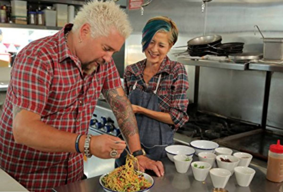 Guy Fieri tries a noodle dish at a restaurant.
