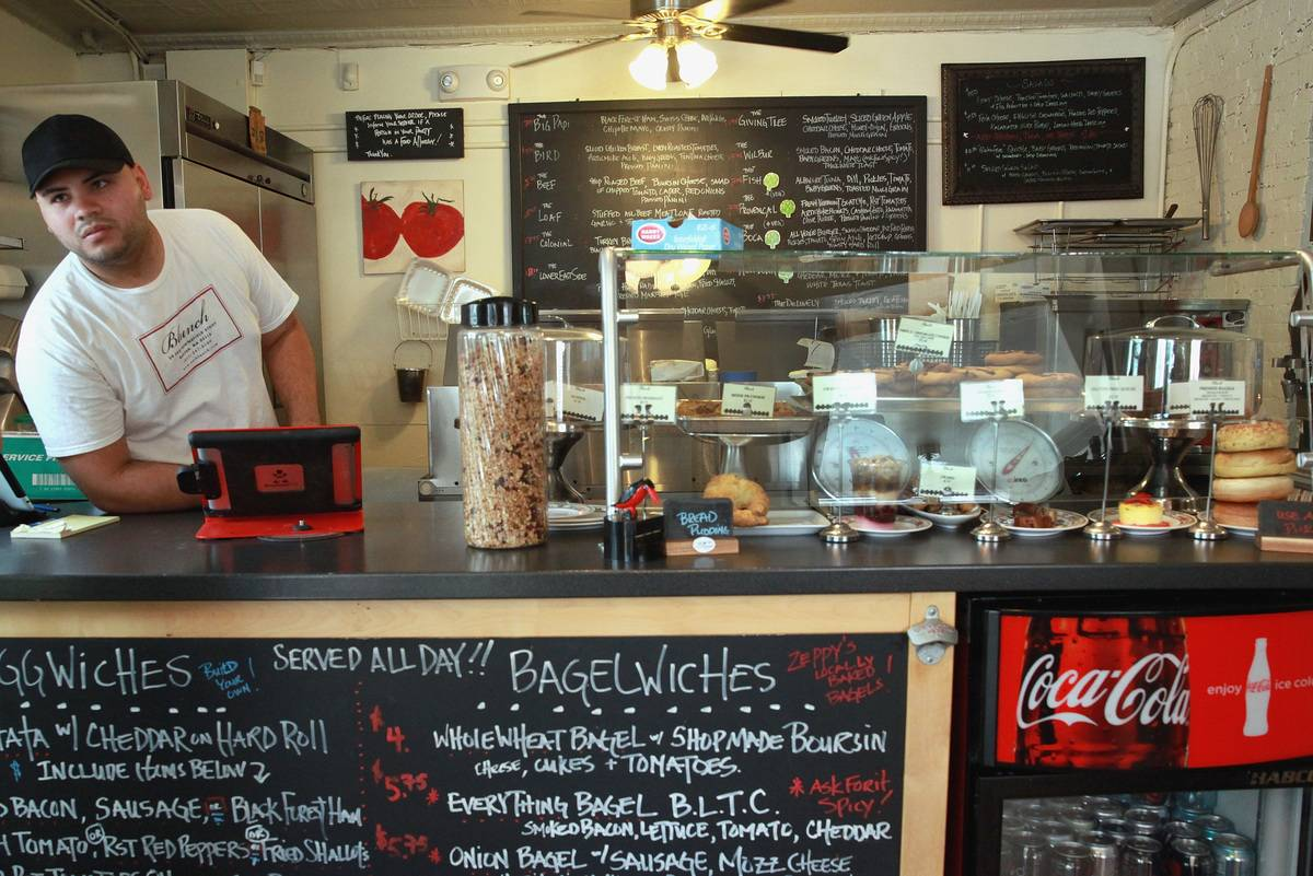Sandwich-maker Andres Oronda stands at the front counter of his restaurant while being featured on Triple D.