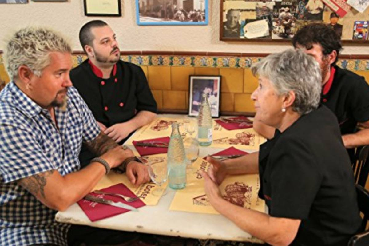 Restaurant owners and chefs talk to Guy Fieri while sitting at a table on Triple D.