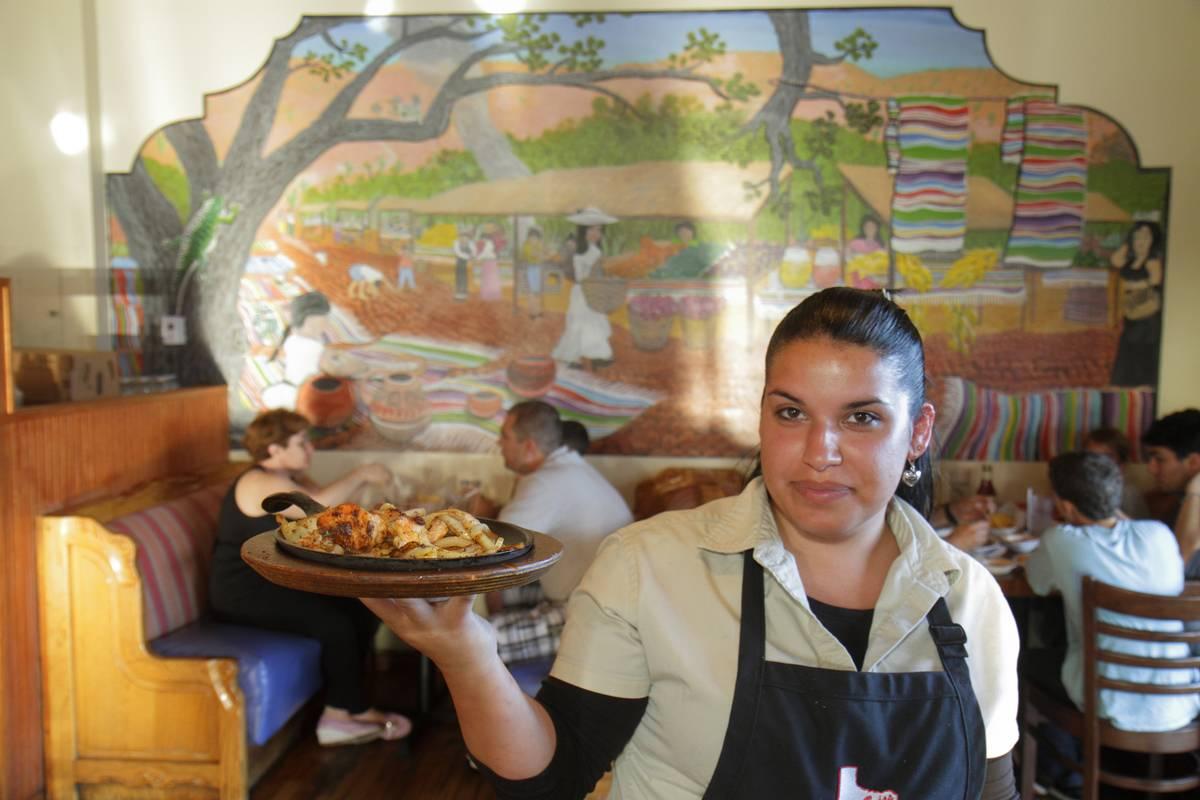 A waitress serving food at Casita Tejas Mexican Restaurant.
