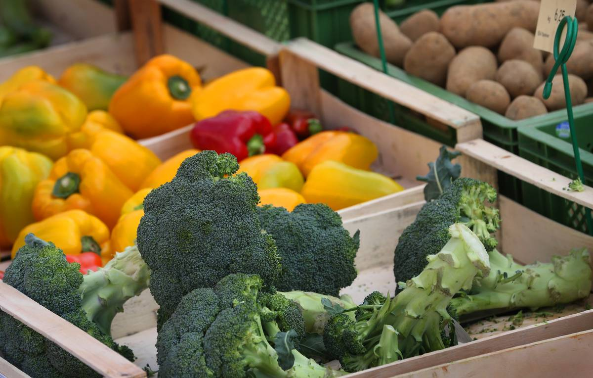 Broccoli and bell peppers are in creates for sale at a market.