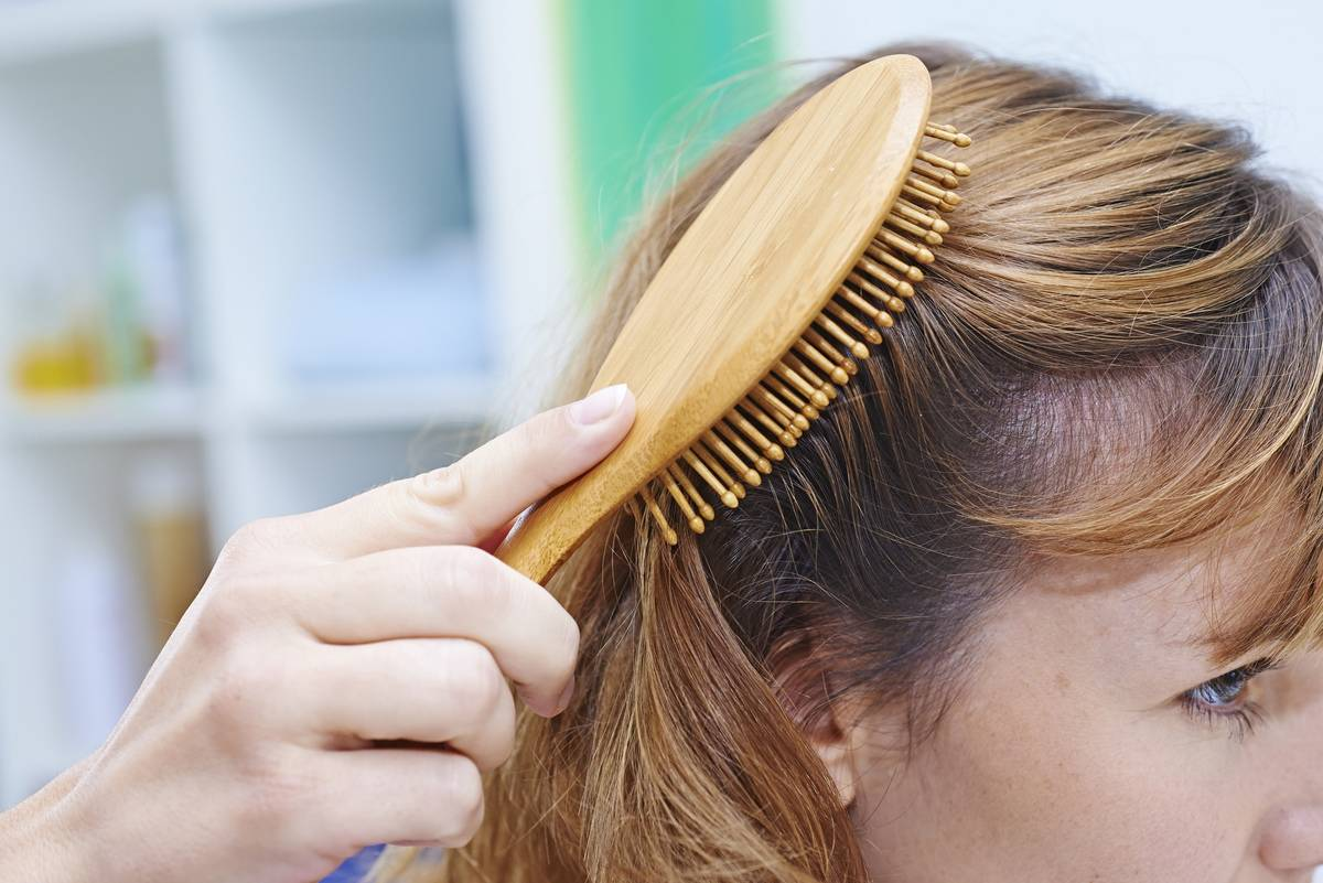 While brushing her hair, a woman reveals a balding spot.