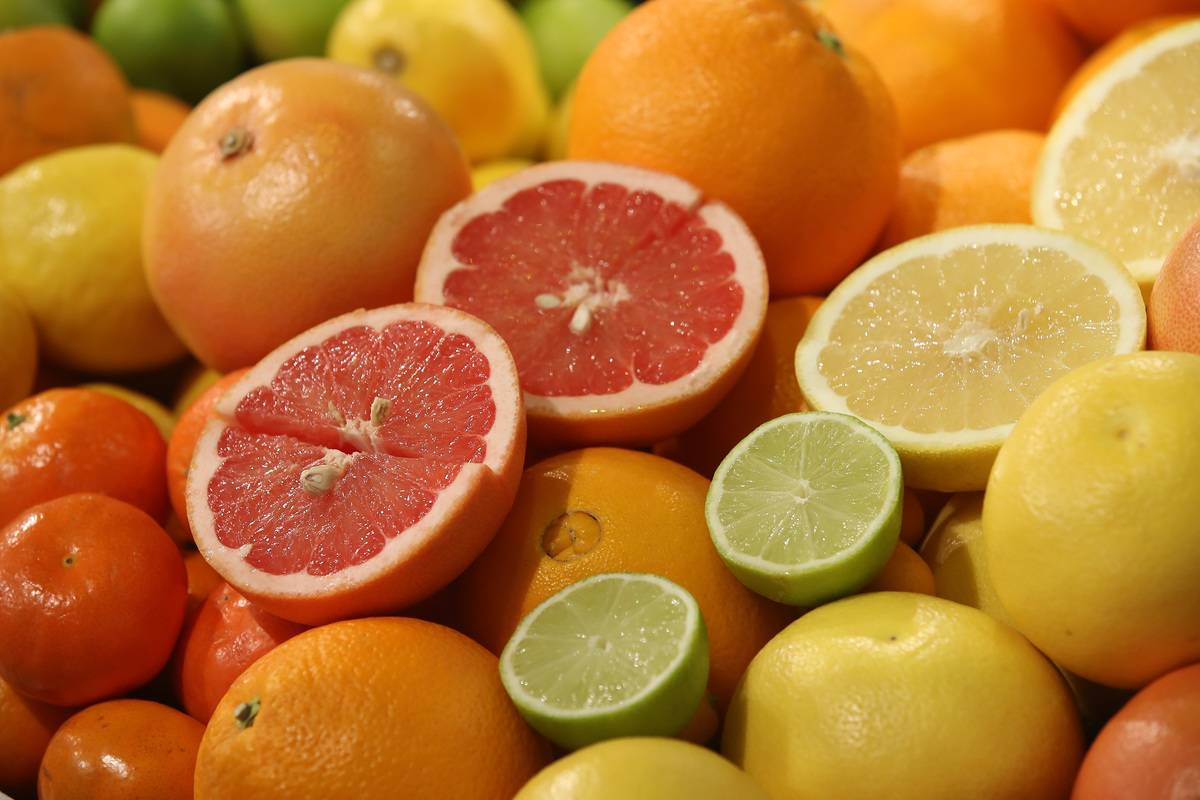 Citrus fruits, including grapefruits, limes, lemons, and oranges, sit in a pile.