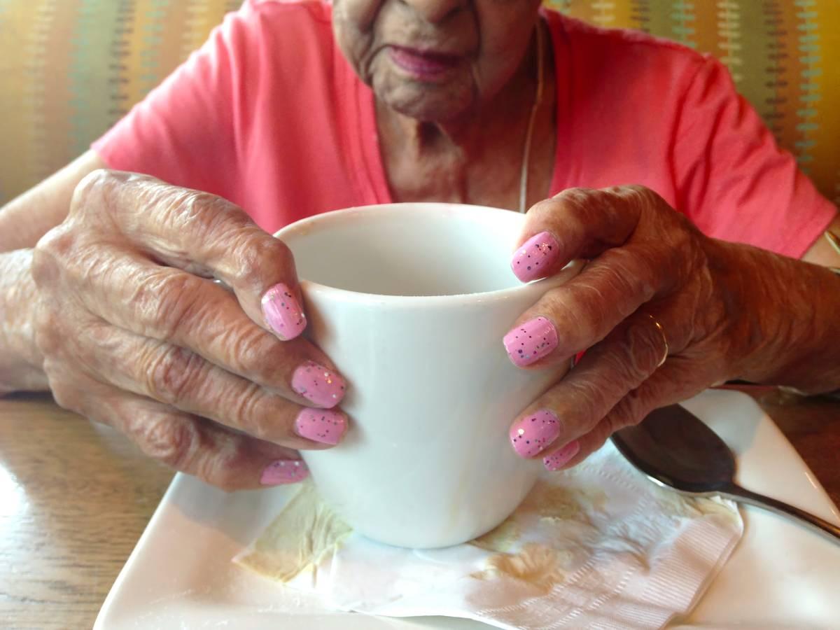 An elderly woman holds a mug of coffee.