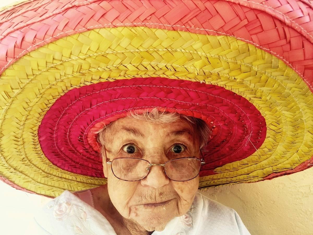 An elderly woman wears a large sombrero.