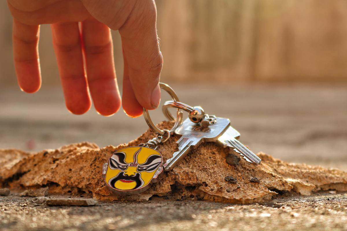 keys with a yellow keychain being pulled from a dirt pile