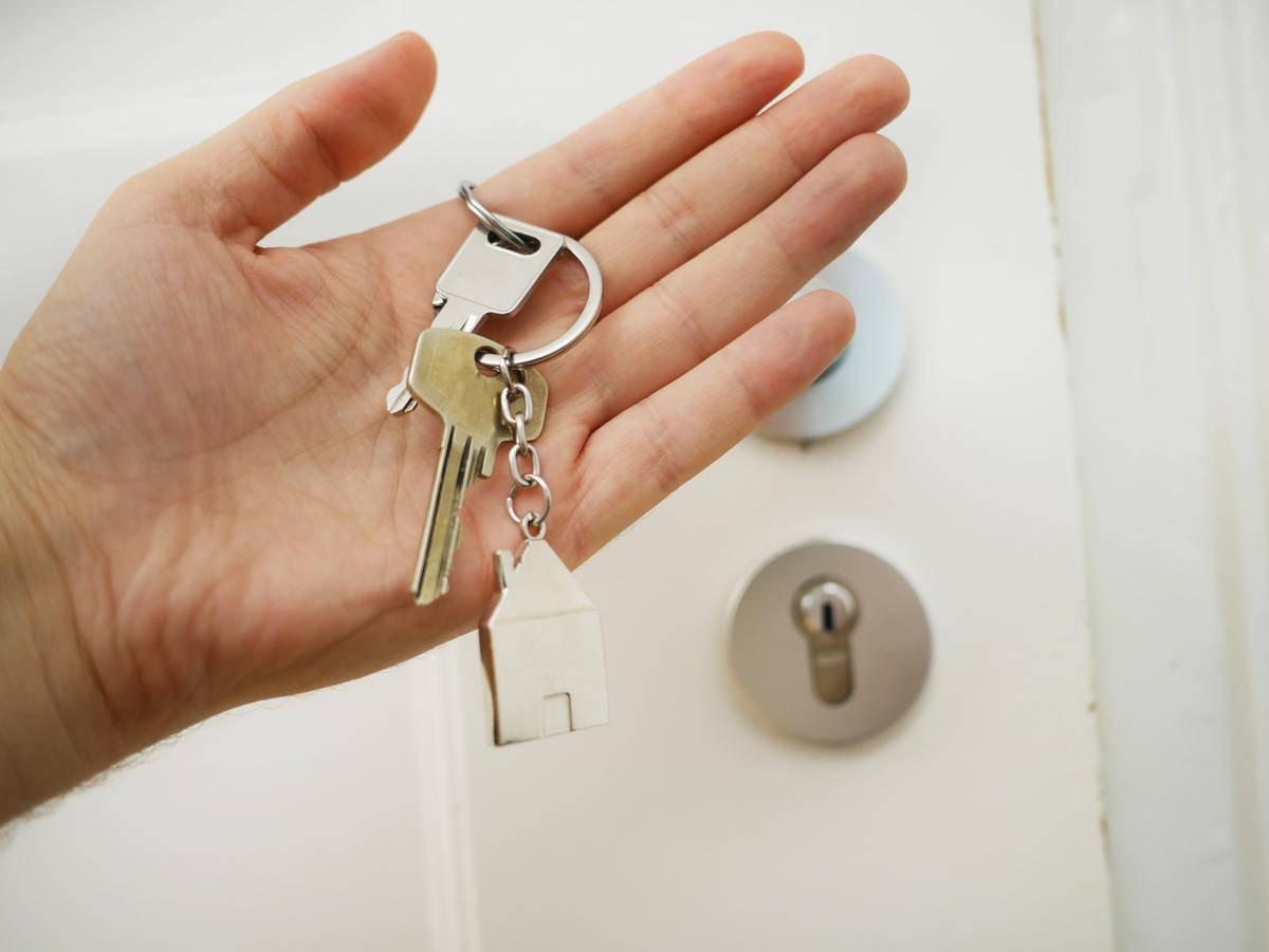 a hand with keys near a door lock
